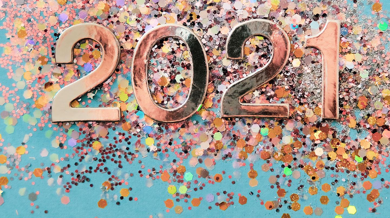 Silvester: Kupferfarbene Buchstaben bilden die Jahreszahl 2020. Darunter liegt buntes Konfetti auf hellblauem Grund.