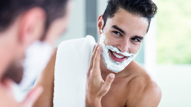 Richtig rasieren, Rasurbrand vermeiden: Junger Mann mit Rasierschaum im Gesicht schaut in den Spiegel..